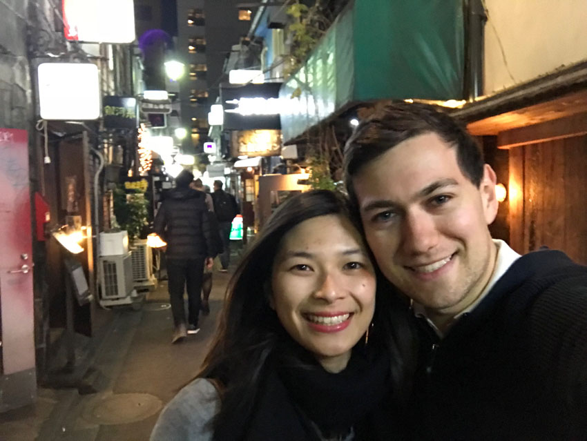 A selfie of me and Nick, both smiling, with neon signs in the background above the bar and eatery entrances in a Golden Gai alleyway