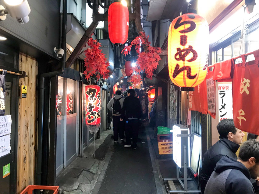 A narrow alleyway with people walking several steps ahead. Red lanterns with Japanese hiragana printed on them hang from some restaurant fronts, people are seen on the right, seated in the restaurants but close to the outside of the restaurant