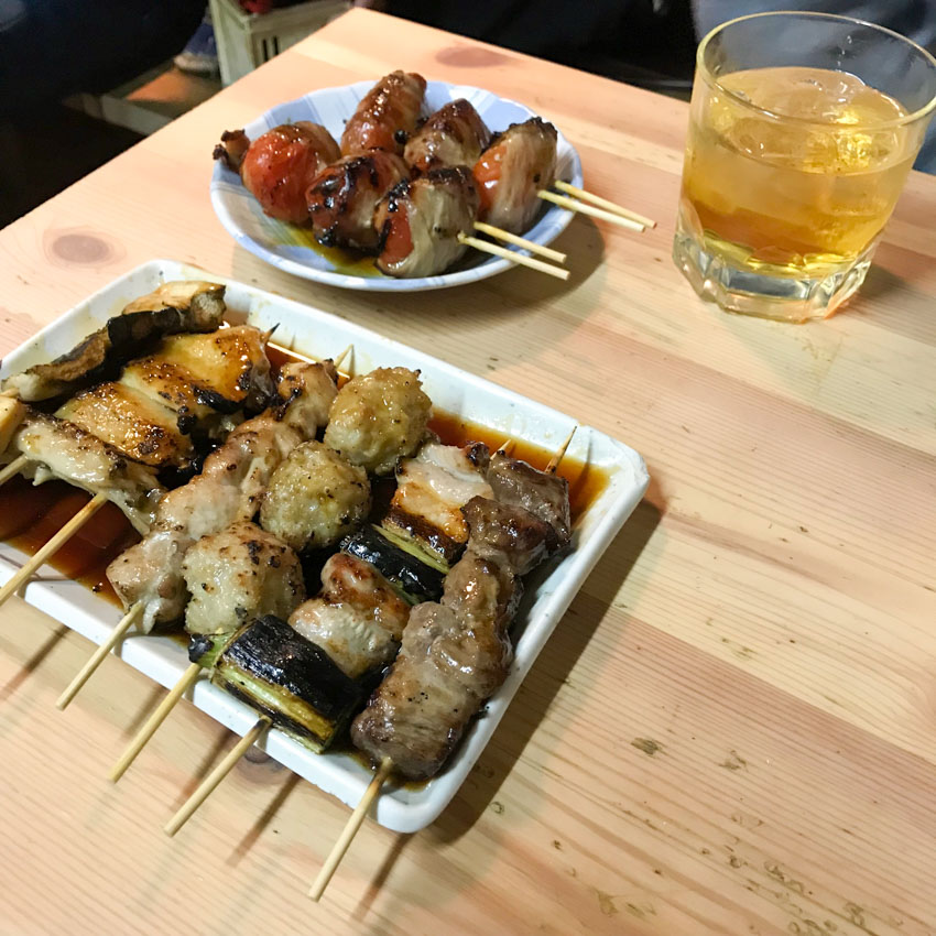 A round dish and rectangular dish on a light wooden table, filled with meat and vegetable skewers, doused in sauce. A short tumbler of umeshu plum wine sits on the table
