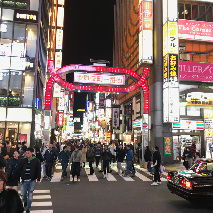 A busy entrance to Kabukichō, off the main road, with a giant pink neon arch as signage. The entrance sits between two high-rise buildings which also have neon signs. Many people cross the crossings that run across the entrance