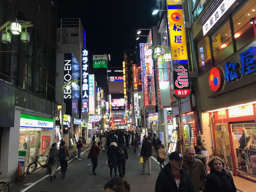 A street at night time, fairly busy with people, with stores and restaurants highlighted by big neon signs