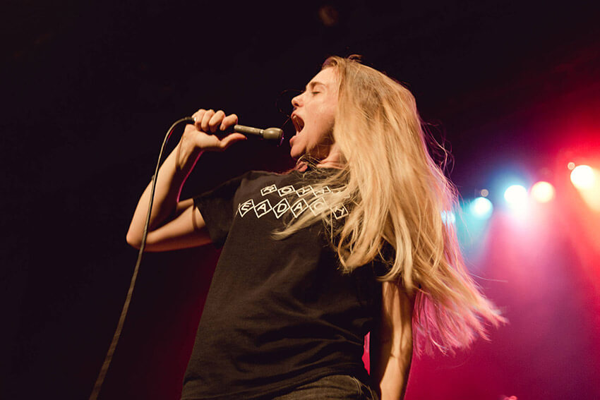 A woman with blonde hair singing loudly into a hand-held microphone on stage