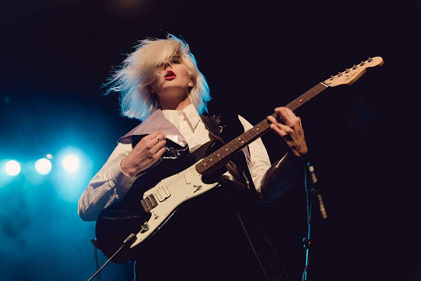 A low shot of a woman with pale coloured hair and red lips, playing an electric guitar with blue lights in the background