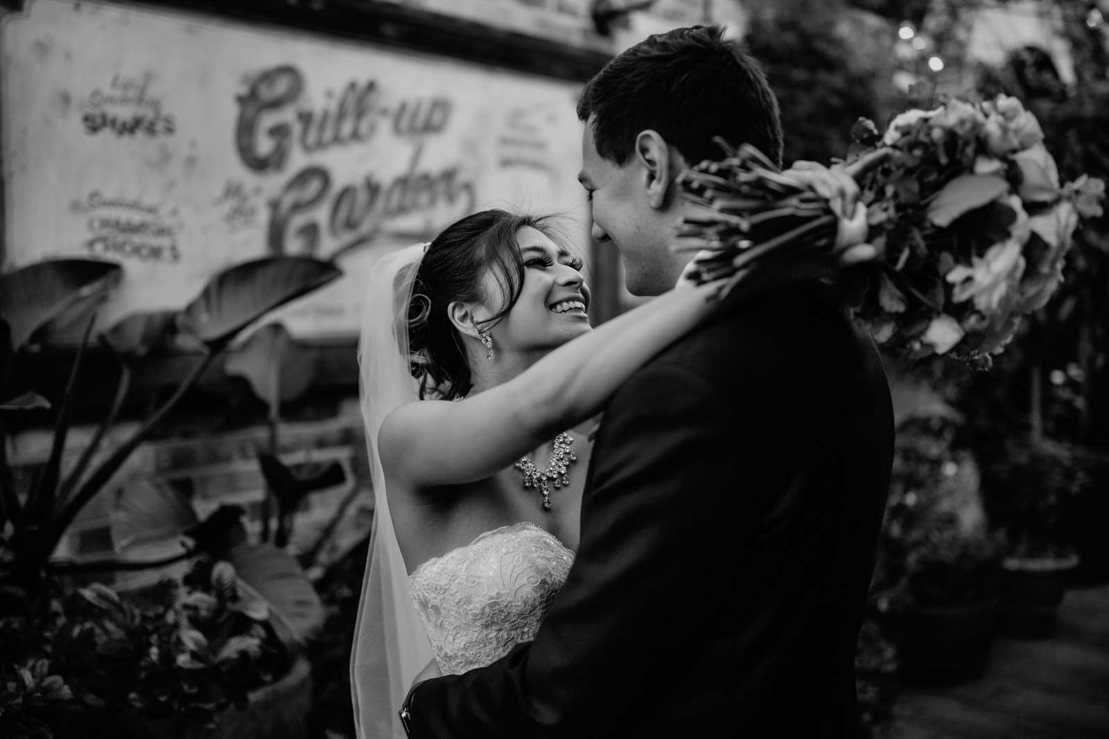 A black and white image of a man and woman embracing on their wedding day. The woman has dark hair in an up-do and a veil hanging from her bun, she has her arms around the man's neck as she holds a bouquet of flowers, both the man and woman are smiling. In the background is an old-style billboard with cursive text on it, and some plants.