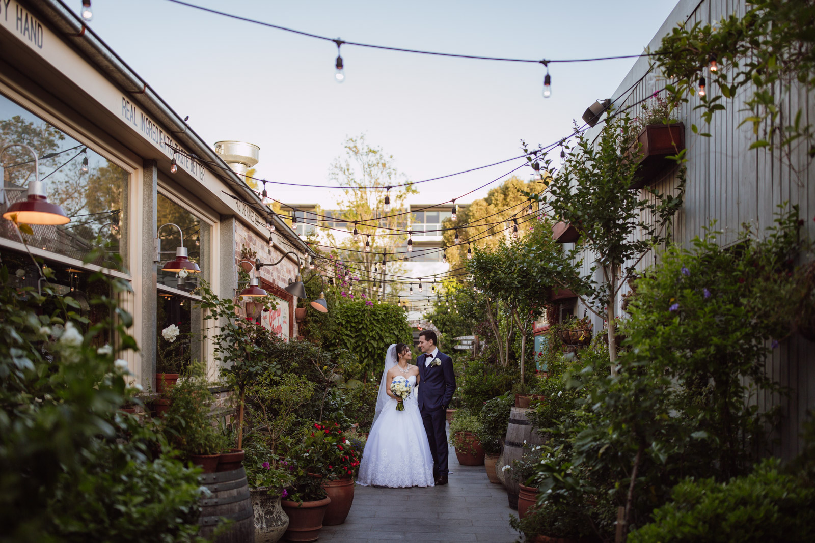 A man and woman on their wedding day in a narrow alley lined with a lot of pot plants. Light bulbs hang from power lines strung across the two buildings on either side. The man and woman are looking at each other and smiling. The woman is wearing a white strapless ballgown and a white veil, and is holding a bouquet of ivory and blue flowers. The man is wearing a navy blue suit