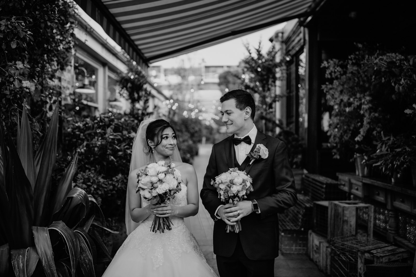 A black and white photo of a man and woman on their wedding day, both holding bouquets of roses. In the background are some plants and wooden crates.