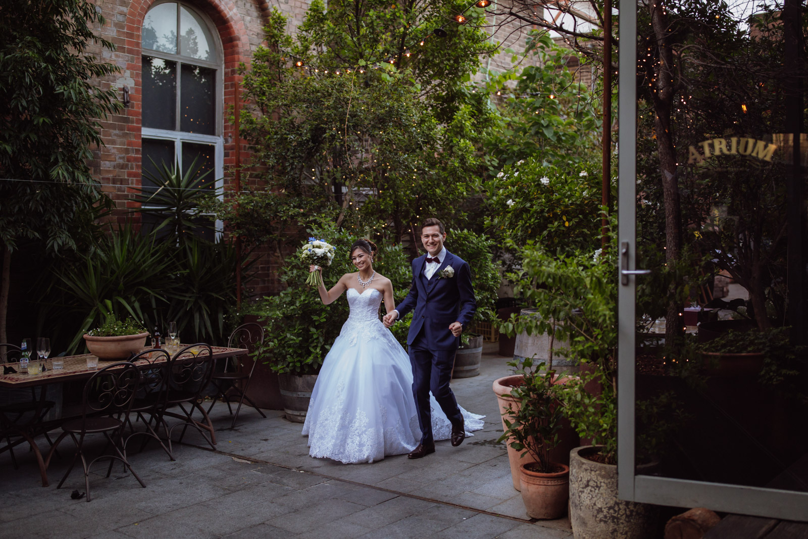 "A man and woman walking holding hands, smiling. The woman is wearing a white wedding ballgown and the man is wearing a navy blue suit. In the background is a wooden table with some ornate metal chairs. The table has some wine glasses on them. In the background is a building and a lot of pot plants, large and small. In the foreground is an open glass door reading ""The Atrium""."