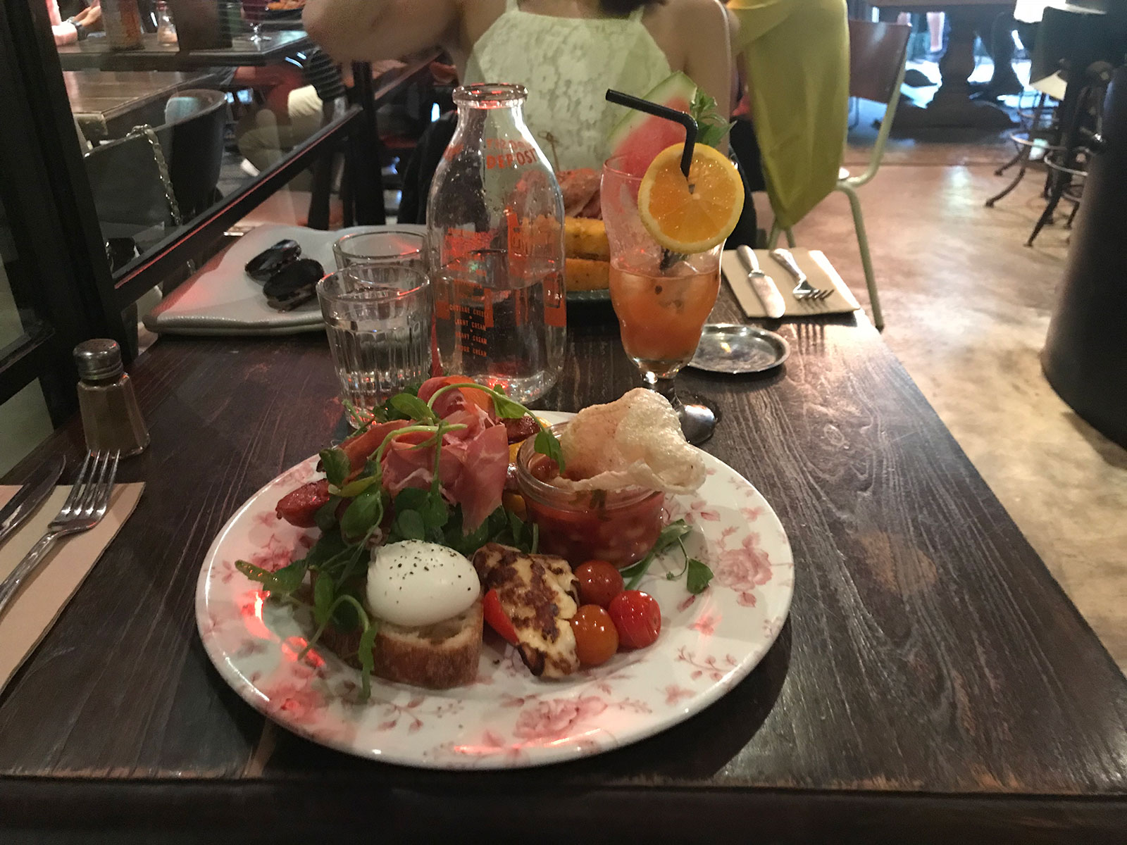 Toast topped with a poached egg, greens, prosciutto and chorizo, with small tomatoes, capsicum and halloumi on the side, served on a white plate with a floral design.