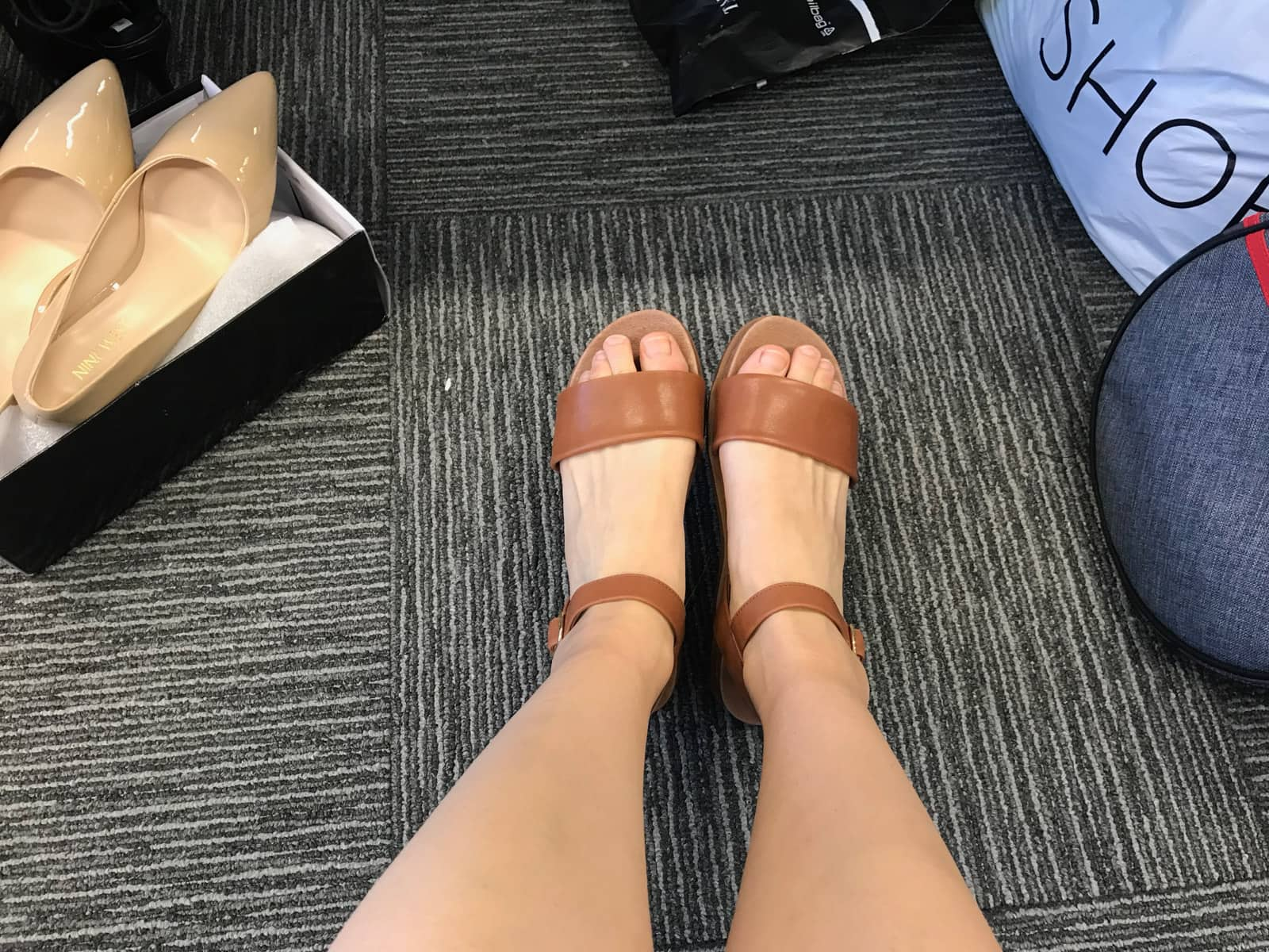 A point-of-view photo of a woman's feet with brown sandals on. In the background is a pair of nude-coloured heels