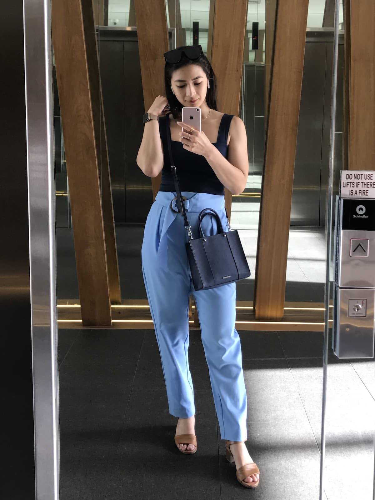 A woman taking a selfie in a mirror. She's wearing a navy sleeveless top with sky blue tapered pants.