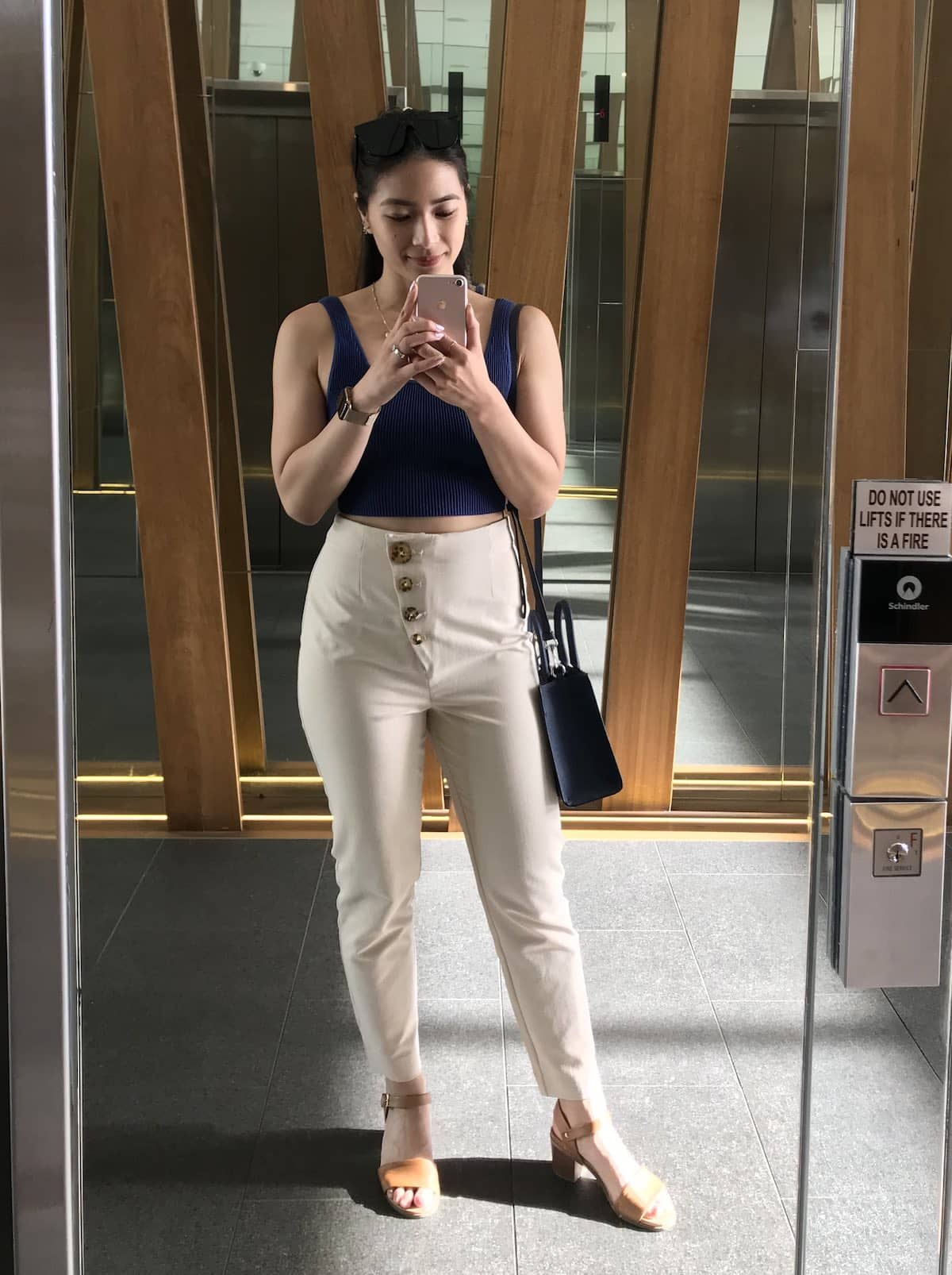 A woman wearing a navy top and beige pants, taking a selfie in a mirror. She has dark sunglasses on top of her head and is also wearing tan sandals.