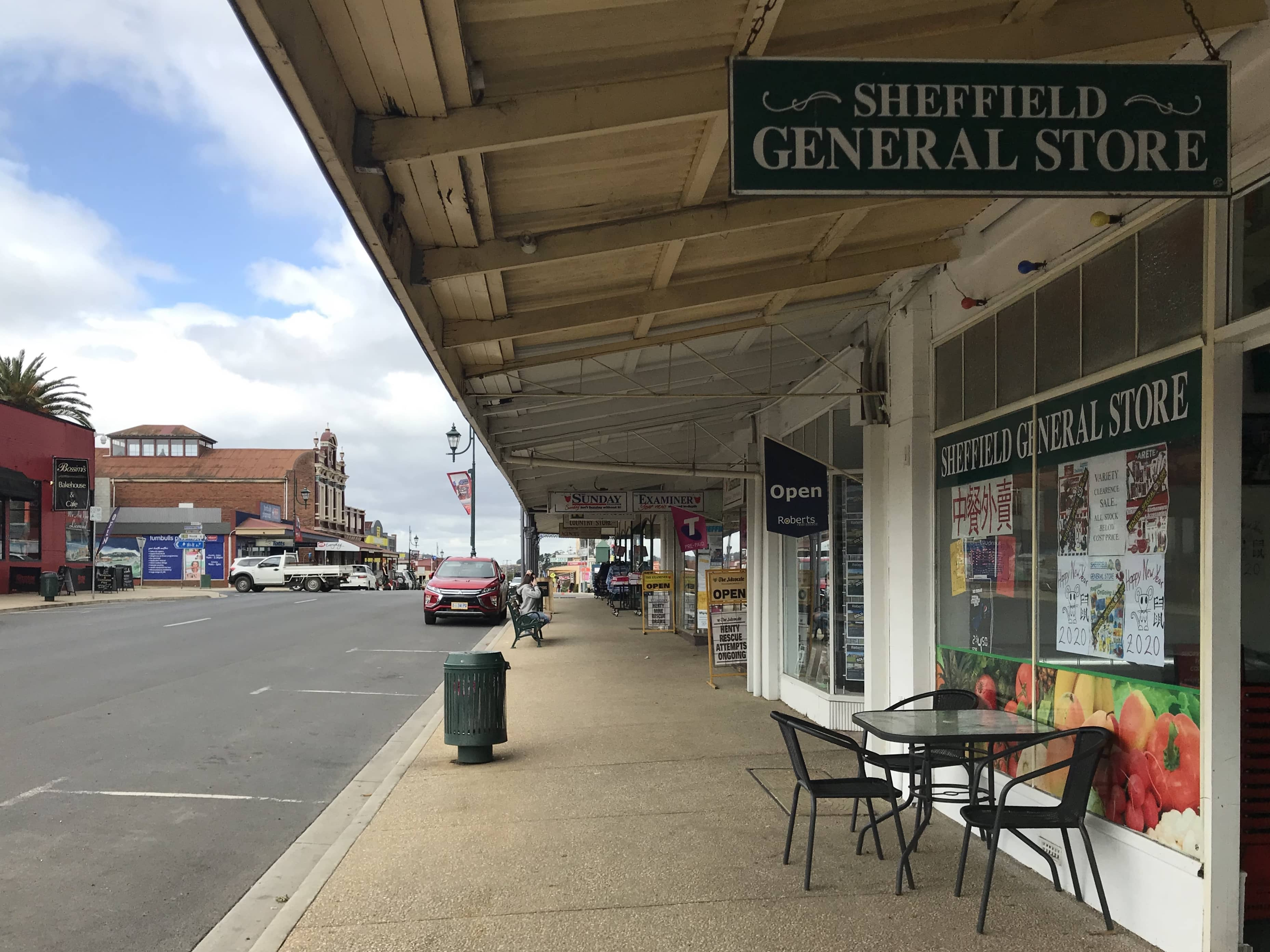 "A storefront at the side of a road of a quiet looking town, with signs reading ""Sheffield General Store"""