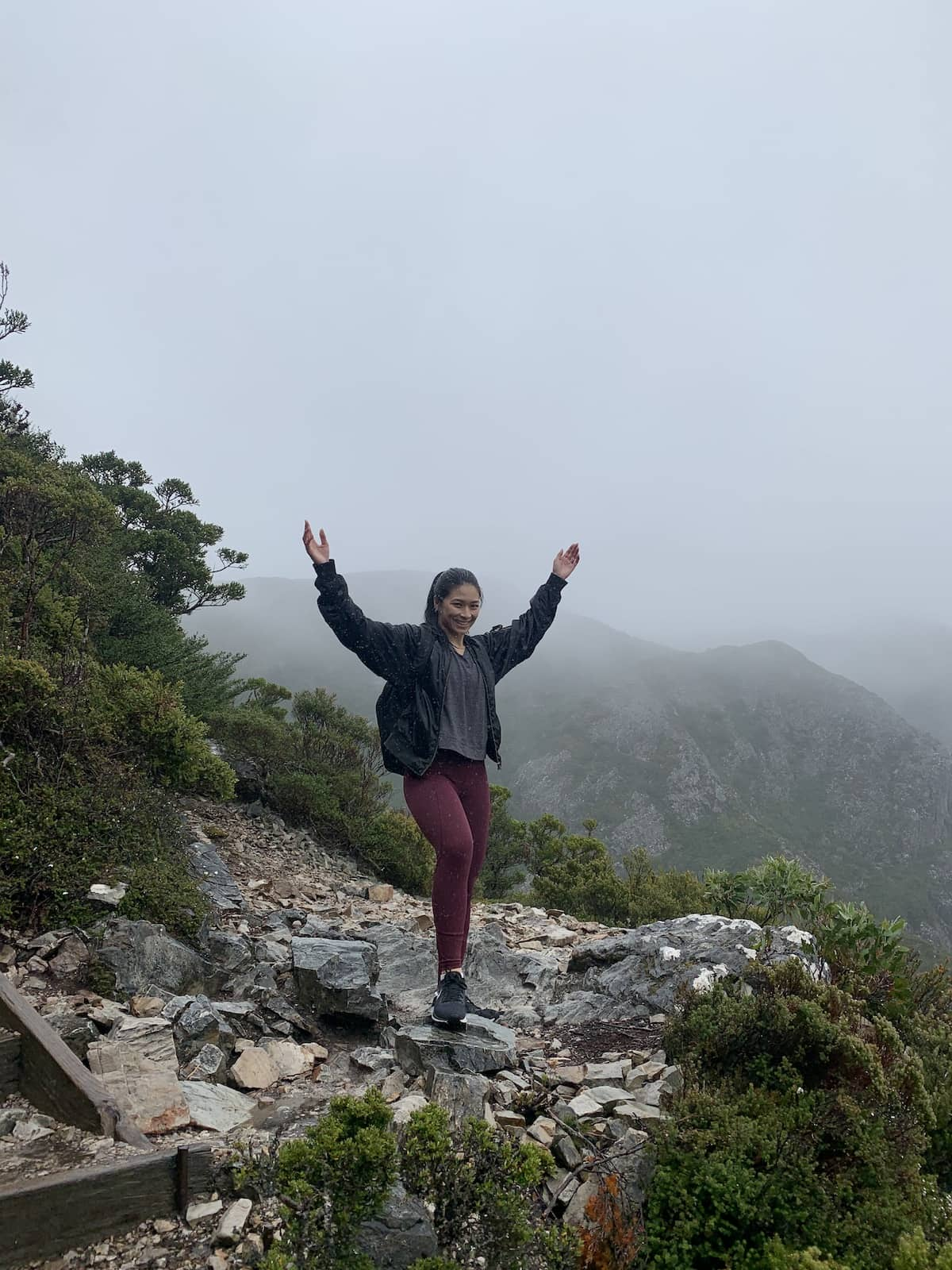 A woman with dark red leggings and a black jacket, with her hands in the air. She's standing on mountainous terrain and it's really cloudy in the background