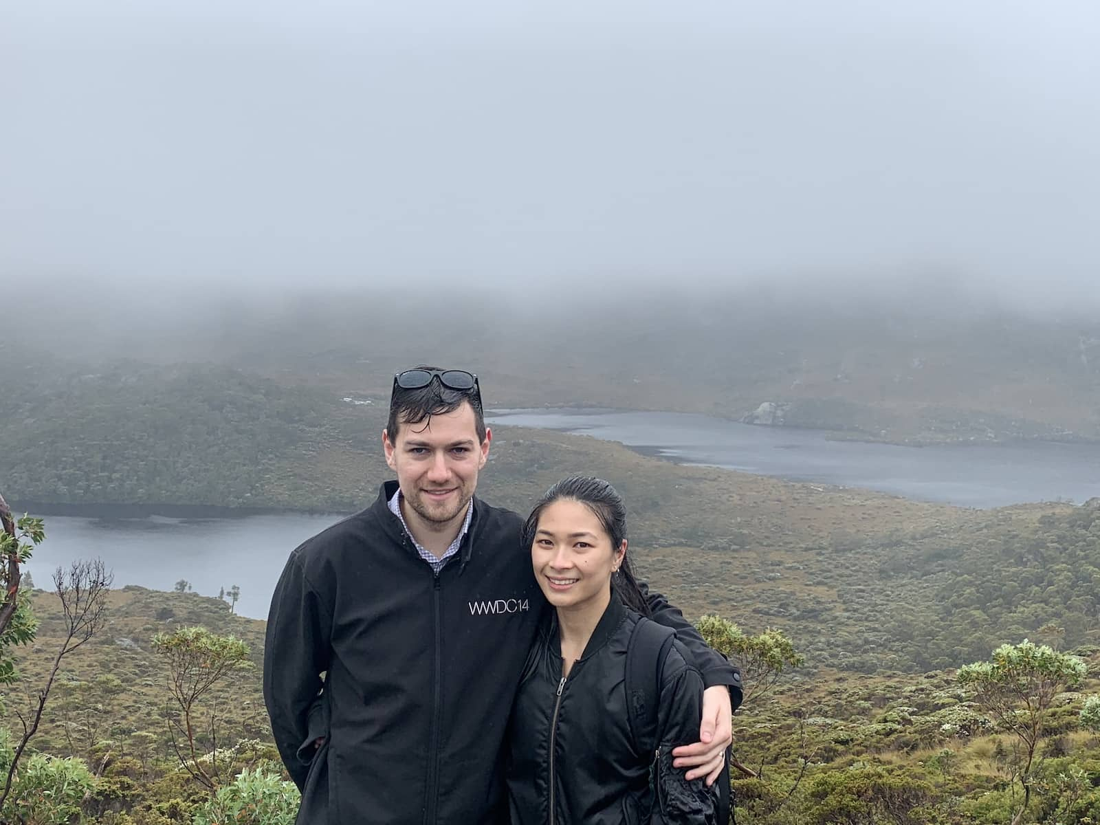 A man and woman with their arms around each other, with some lakes in the background. They are damp from the rain