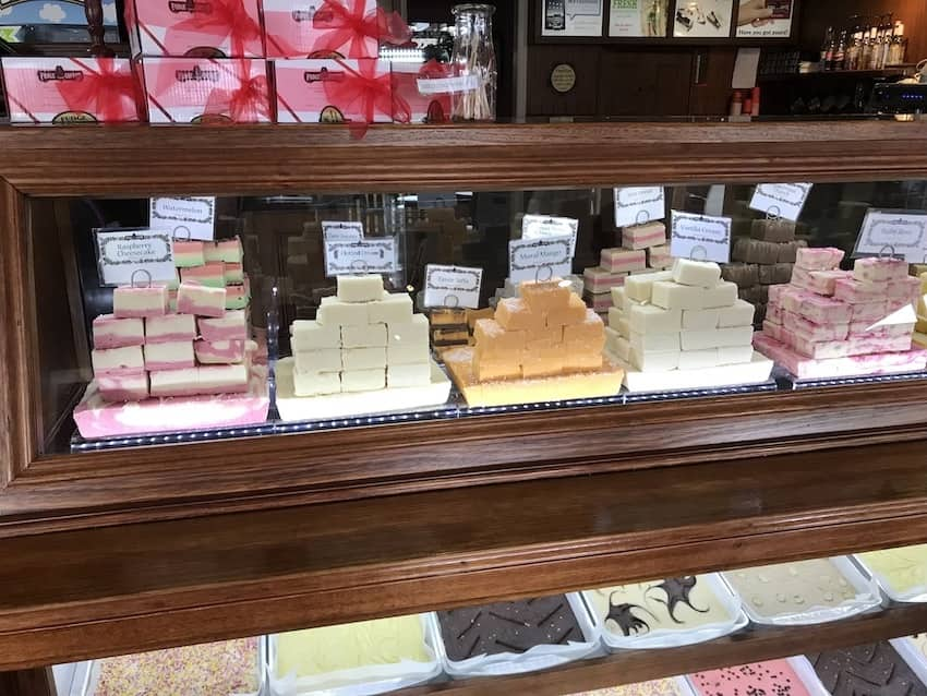 A small glass display in a store, showing various flavours of fudge.
