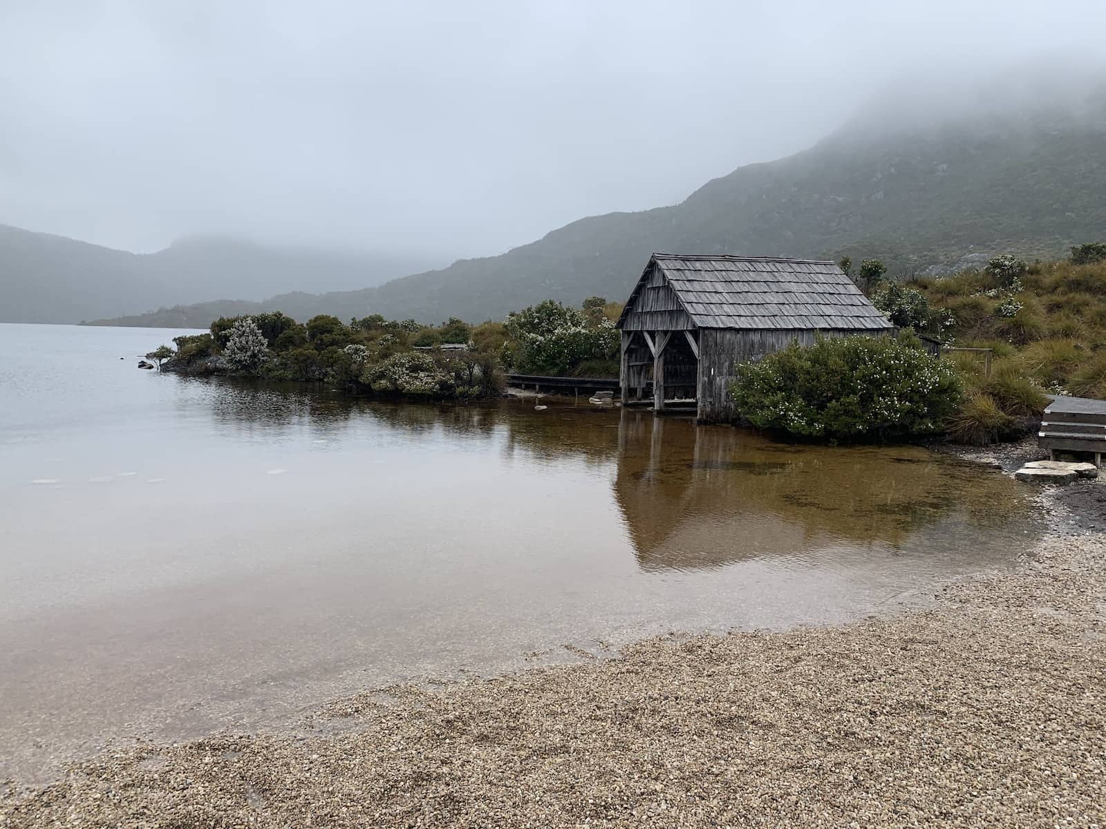 A boat shed at the side of a lake, on an overcast, wet day