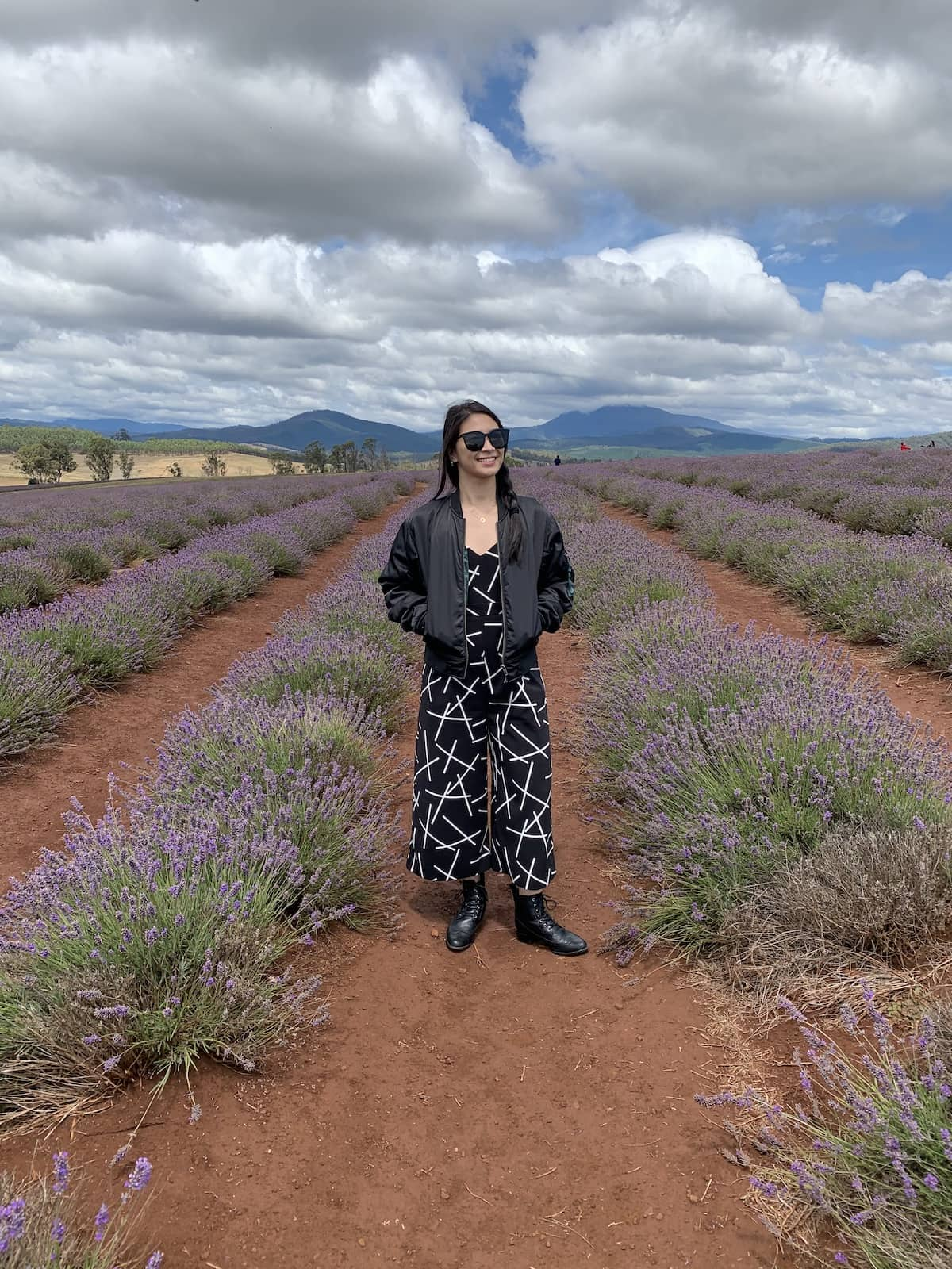 A woman in a black patterned jumpsuit and black bomber jacket, standing between rows of planted lavender. She is wearing black sunglasses.