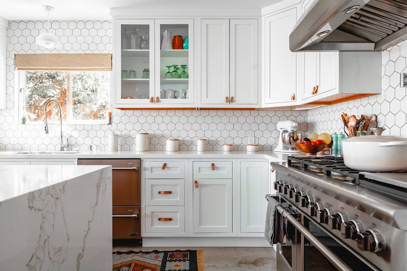 A brightly-lit kitchen with white walls of honeycomb-shaped tiles. The kitchentop on the left is made of white marble, and an oven sits on the right. Ahead, some white cabinets can be seen, some with windows