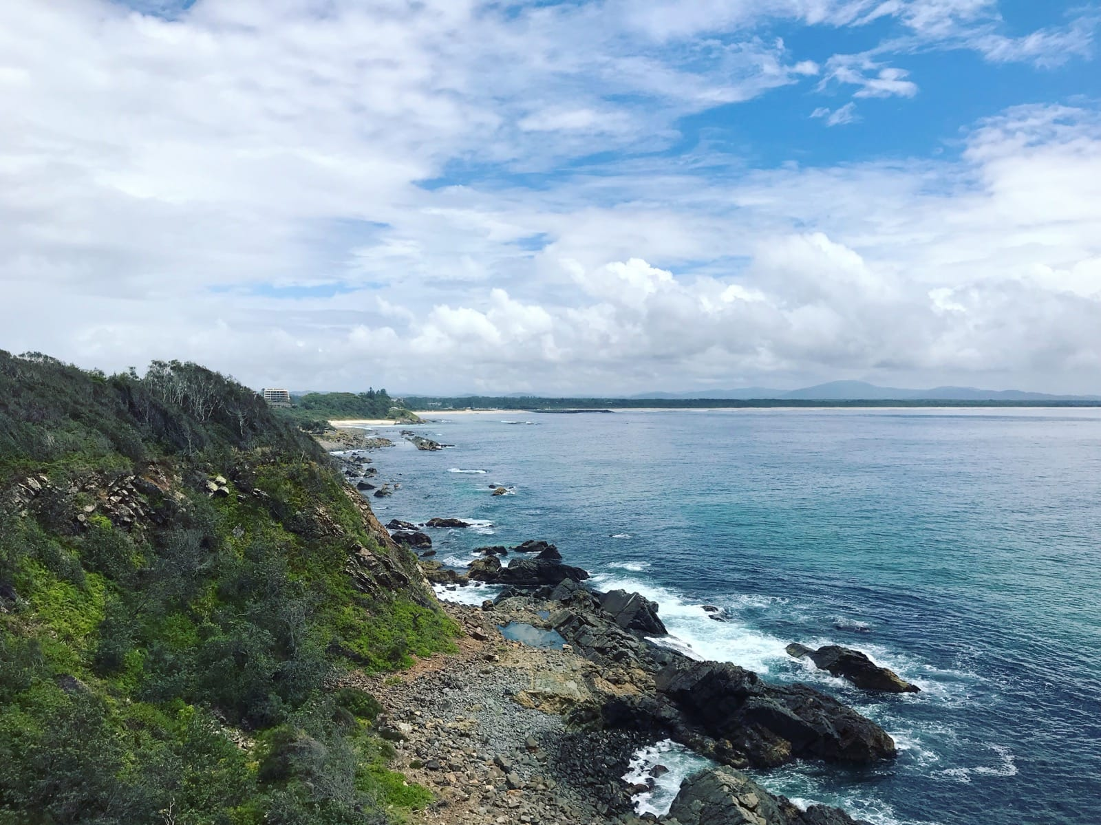 A view from a high vantage point of a high part of grassy bushland leading to the ocean. A rock beach separates the land from the water. The sky is blue but has many clouds