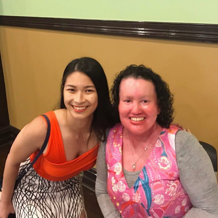 Two women smiling, one has light skin and dark straight hair, and the other has dark curly hair and pink skin. They are both wearing bright orange and pink.