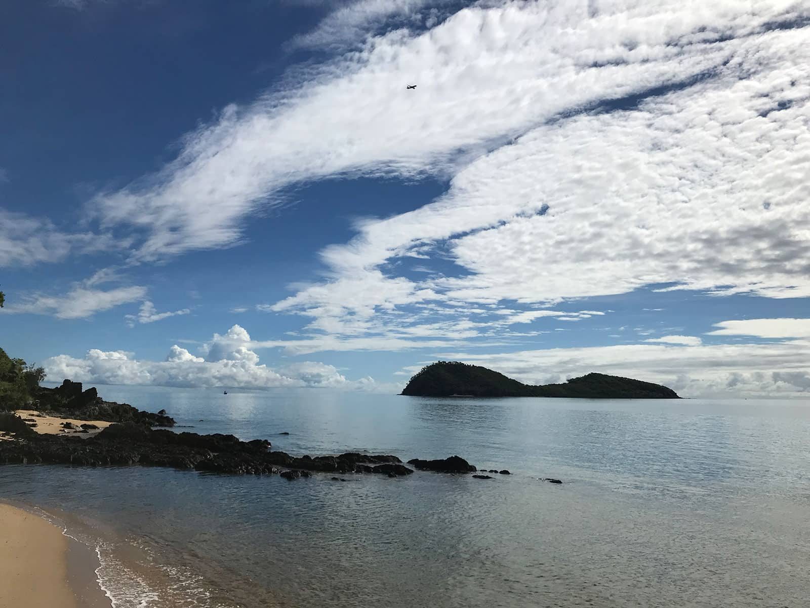 A view of the shore of a beach, with vast stretches of white clouds in the blue sky. The water by the beach is blue and there are some rocks in the shallow part of the water.