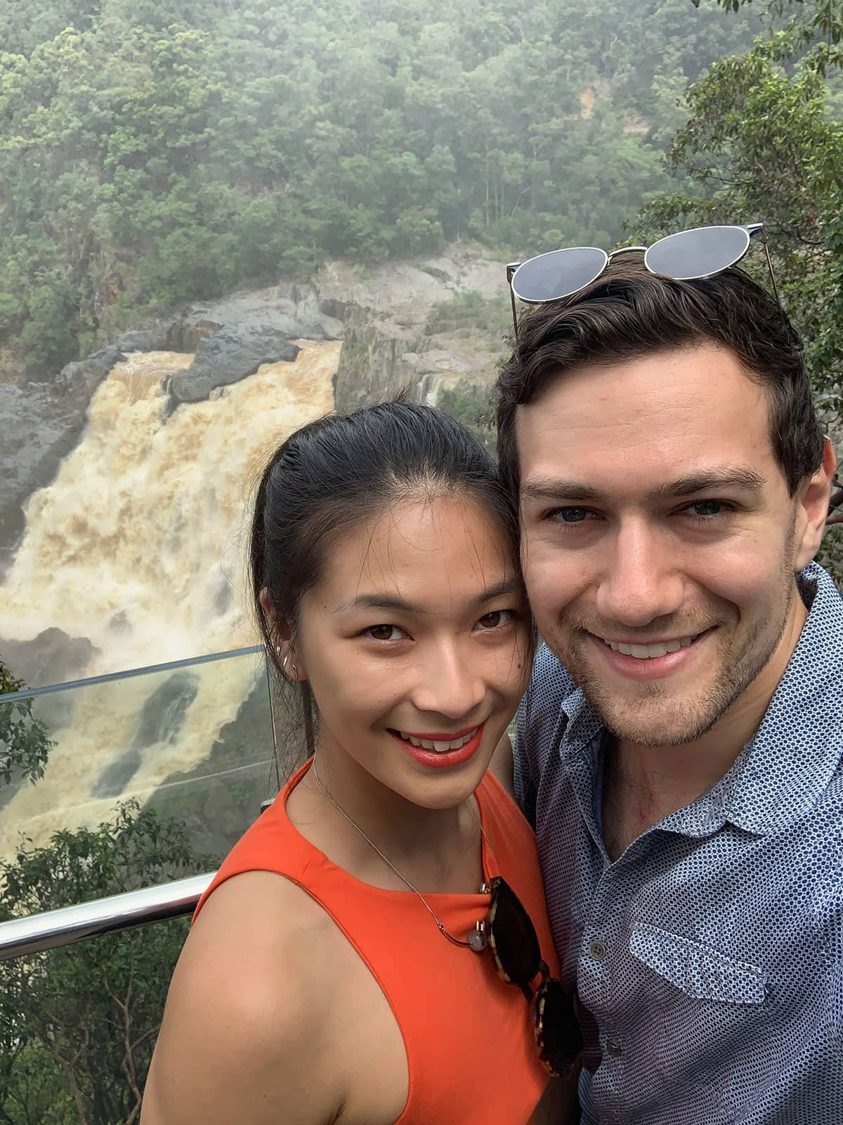 A selfie of a man and woman, smiling, with a murky waterfall behind them. It's quite misty. The woman is wearing an orange top and the man is wearing a patterned blue shirt.