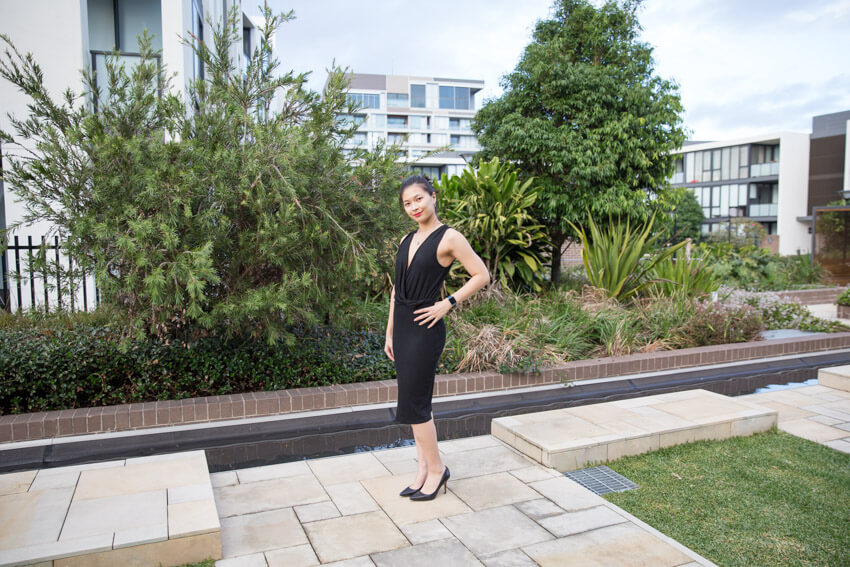 A woman in a black dress with a plunging neckline. She is wearing black pumps (heels) and standing on yellowed concrete. Her left hand is on her hip and her body is angled slightly towards the camera.