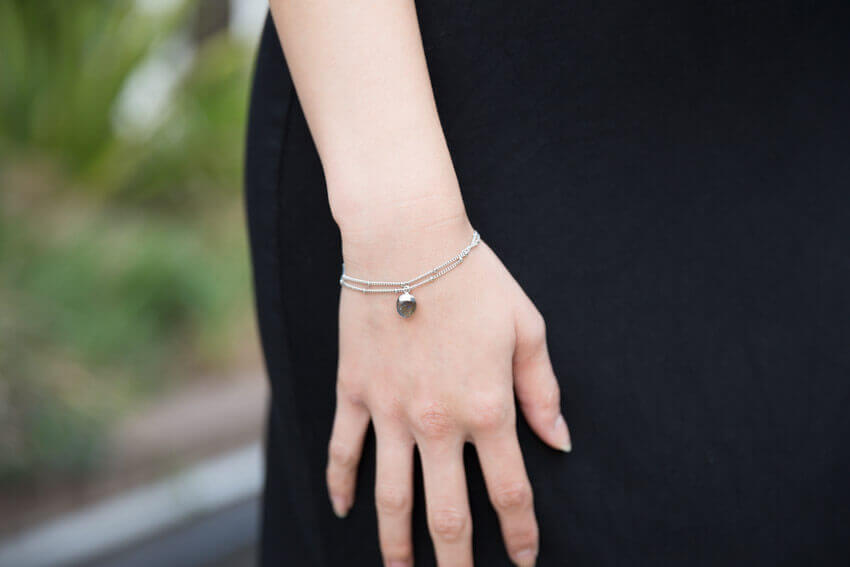 Close shot of a woman's wrist wearing a silver bracelet with two chains. From one chain hangs a labradorite pendant.