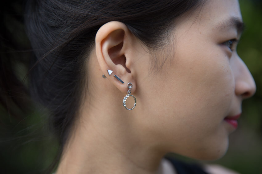 A close view of the right side of the woman's face, with her earlobes in focus. She has three earrings, two are studs and the bottommost one is a ring shape.