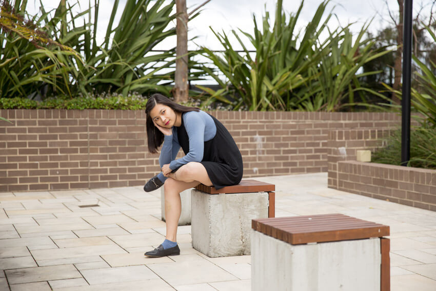 The same woman from other photos on this webpage, sitting on a concrete cube with a wooden top. She has the ankle of leg propped up on her opposite thigh and is leaning forward using her arm on her lap as balance. Other concrete cubes surround the one she is sitting on.