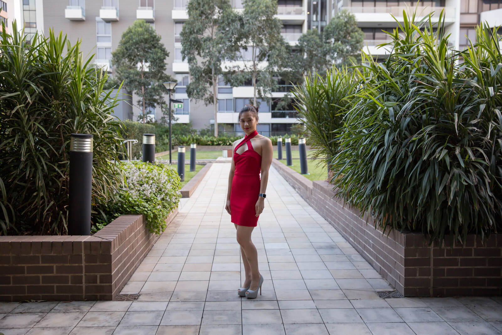 A woman wearing a red dress which has a cross-over front strap above the bust, her dark hair worn in a bun. She is wearing silver high heels and standing on a path with short brick walls and plants and grass outside of the walls.