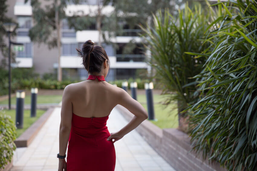 The same woman in the other photos on this webpage, facing away from the camera. She is wearing a red halter dress that shows her upper back. Her right hand is on her hip and her hair is up in a bun.