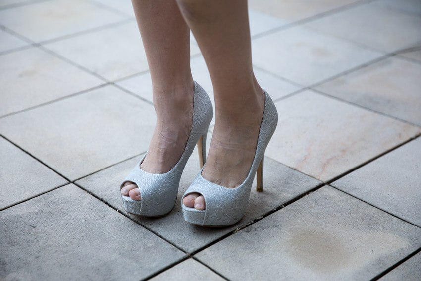 A woman's feet in a pair of sparkling silver platform heels.