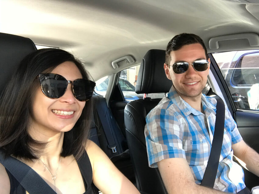 A man and woman with sunglasses, sitting in the front row of a car, smiling