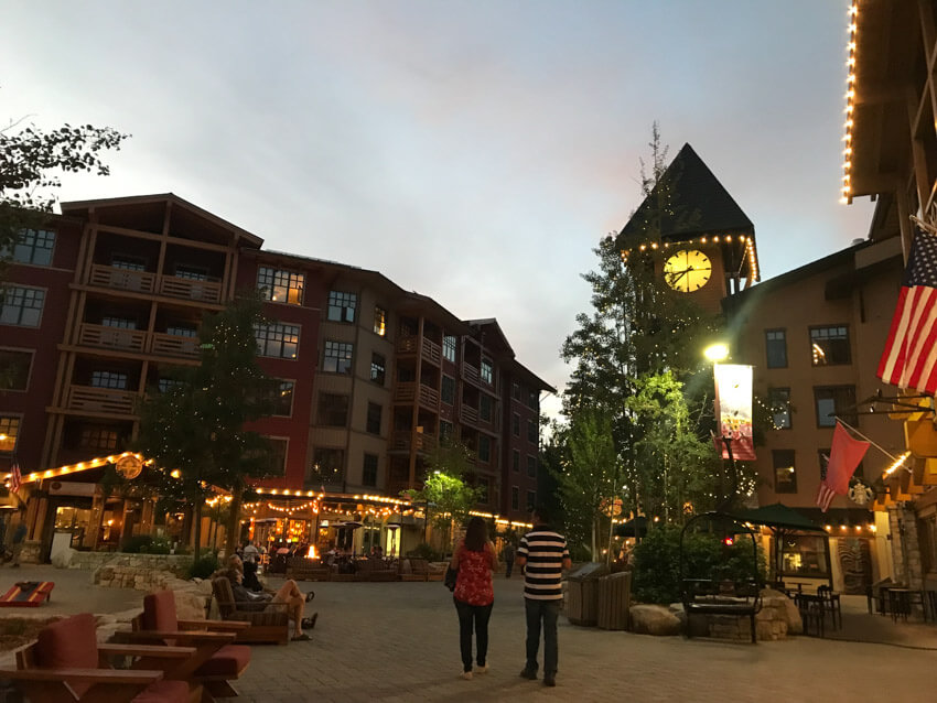 A town plaza at twilight. There is a clock tower and restaurants that are lit with rows of small lights. In the foreground are outdoor chairs, some people sitting and a couple walking.