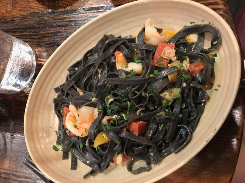 A beige oval bowl filled with black squid ink spaghetti, some prawns, and a dash of herbs