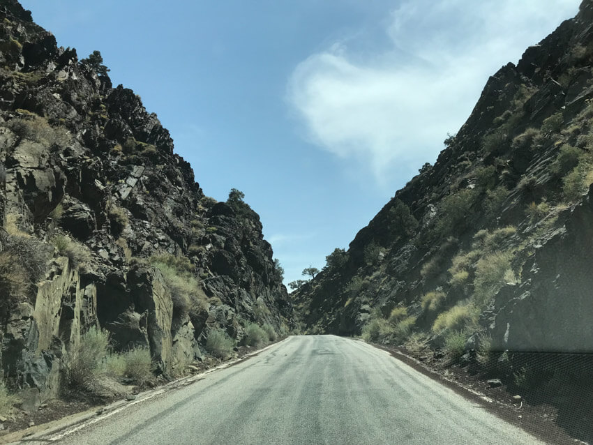 An unmarked road leading into the distance, lined at the sides with high formations of dark, almost black rock. There are weeds in the rocks.