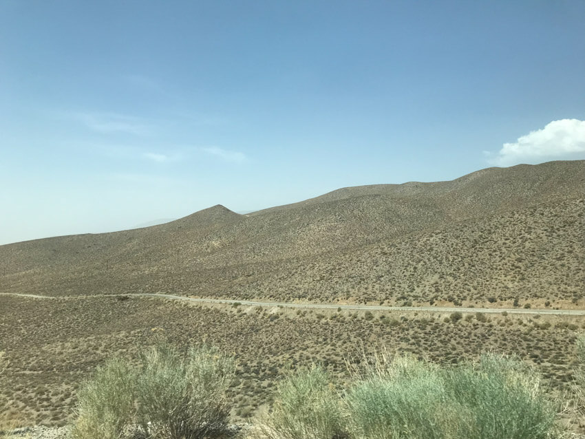 A slightly mountainous desert-like area with a thin road stretching from left to right.