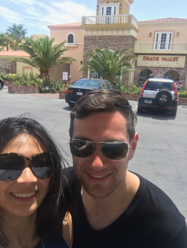 "A man and woman wearing sunglasses, smiling. They are in a car park in front of a building that reads ""Death Valley Nut & Candy Co."""