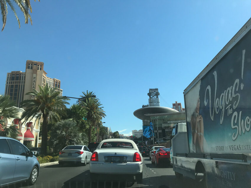 "A multi-lane road with some traffic, as seen from the view of a car. There is a vehicle to the right with a billboard on it that reads ""Vegas!"". In the distance are palm trees down the left of the road, and some tall hotels."
