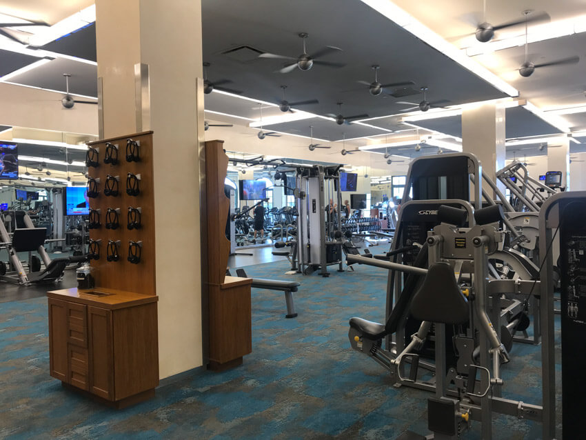 An indoor gymnasium with several machines. In the foreground is a wooden rack with headphones hanging from it.