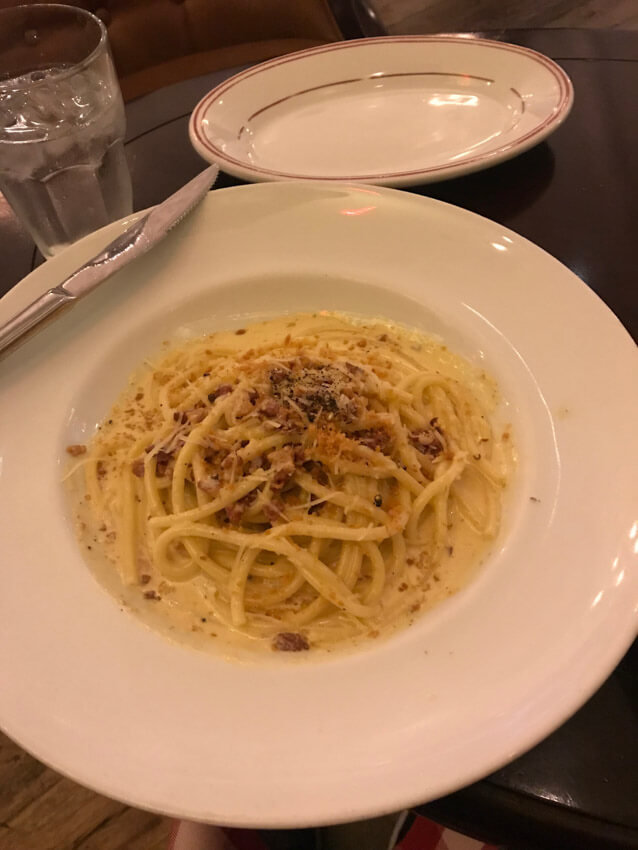 A white plate of spaghetti carbonara