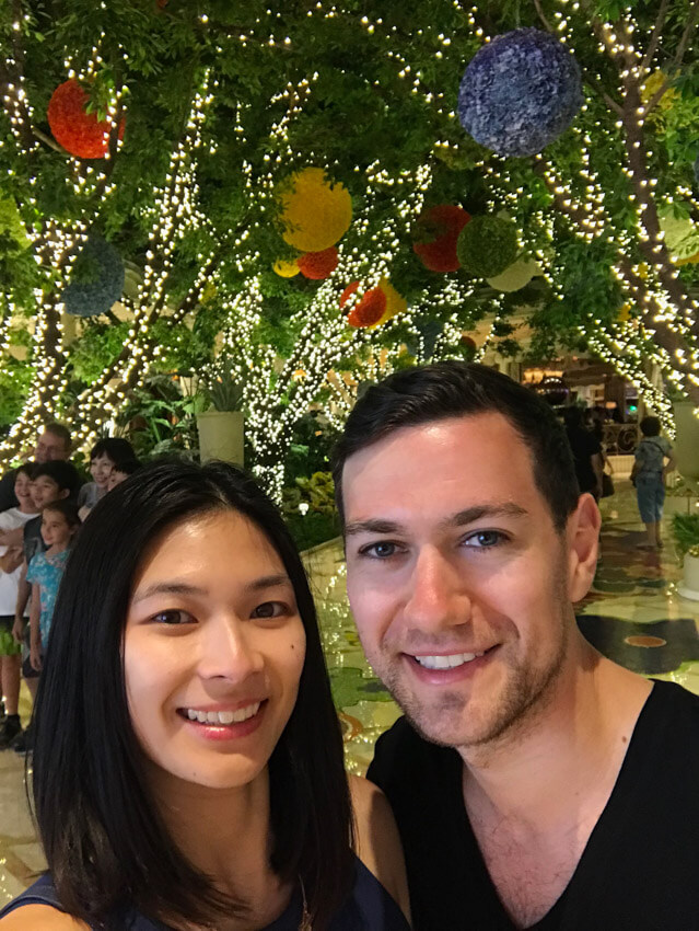 A man and woman smiling, with trees in the background that are decorated with fairy lights