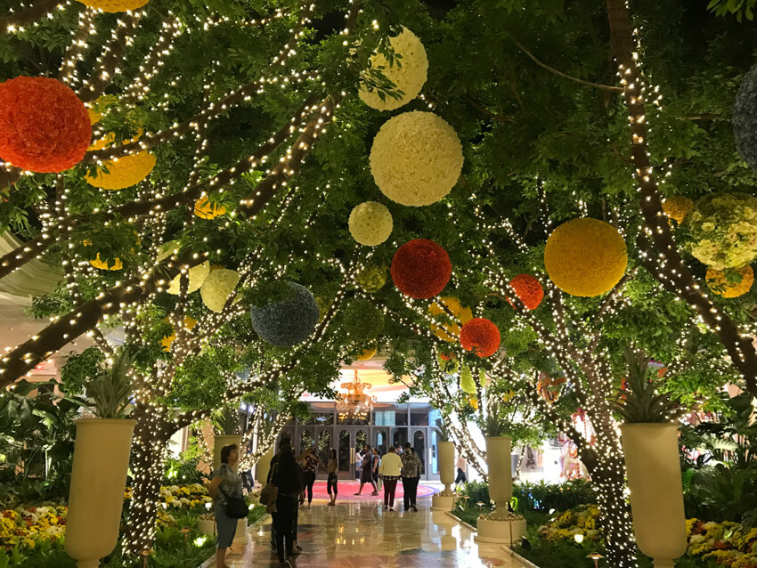 Fake trees adorned with fairy lights and large baubles made of flowers, forming a canopy over an internal marble floor
