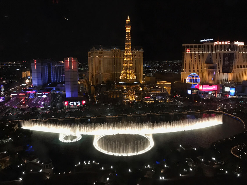 A nighttime view of a city, with an arrangement of lit-up water fountains. In the background is a replica of the Eiffel Tower