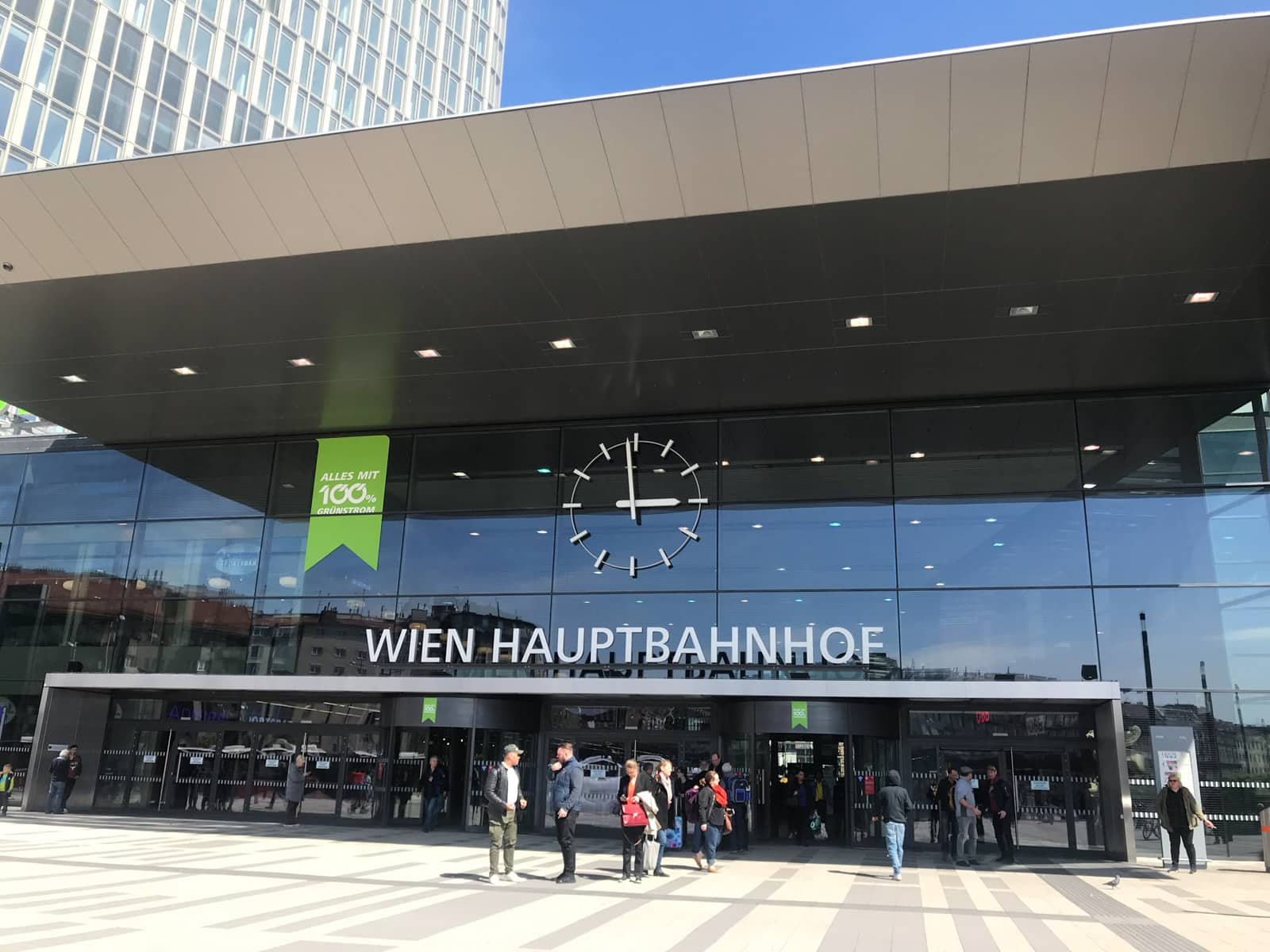 "The entrance of a building with the sign ""Wien Hauptbanhof"" above the glass doors. An analog clock on the building face reads that it is almost 3:00pm"