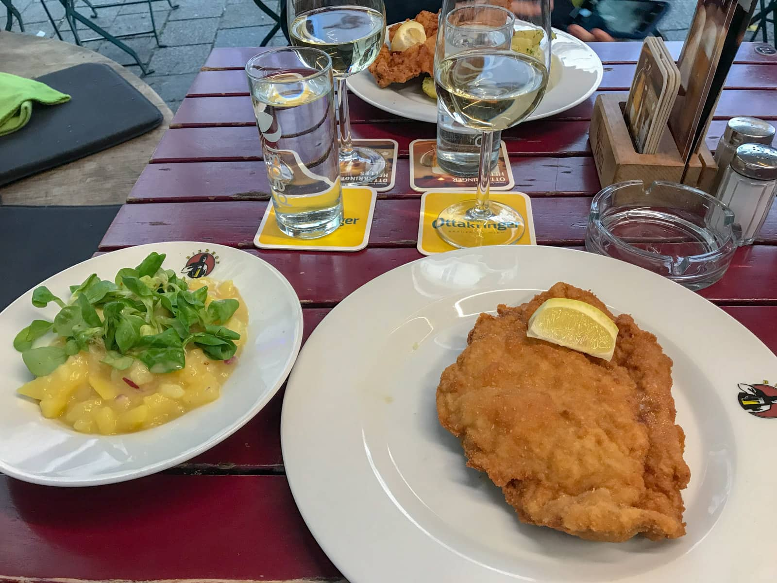 Two plates on a table, one with potato salad and the other with schnitzel and a lemon on top