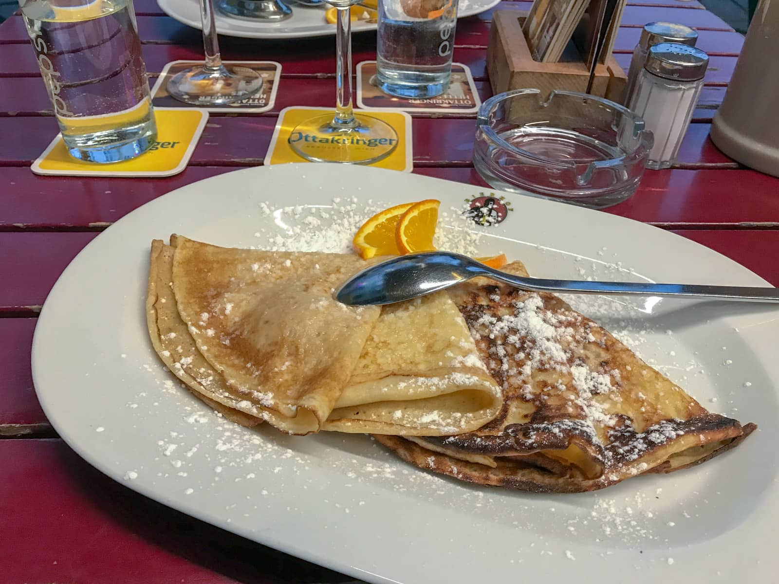 Folded pancakes on a plate drizzled with icing sugar