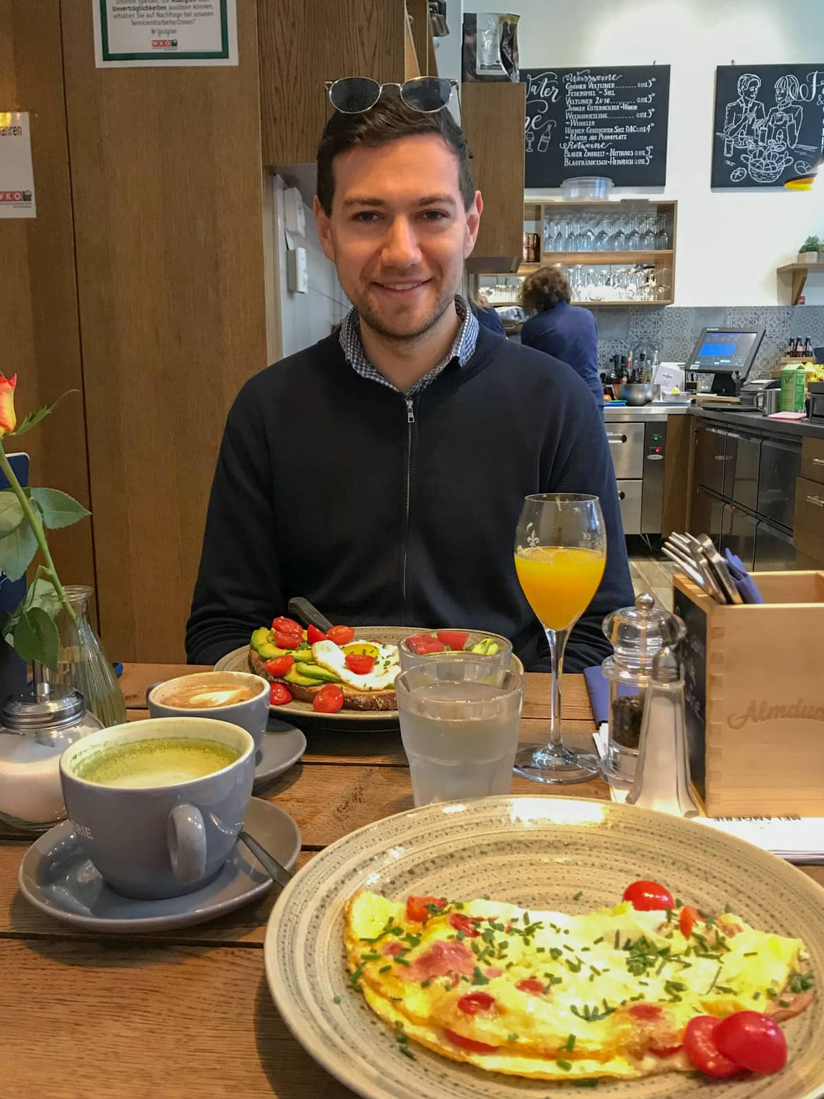 A man smiling, sitting at a table which has breakfast served. There are two plates, one with an omelette and the other with avocado on toast. There is orange juice in a glass and a couple of coffees on the table