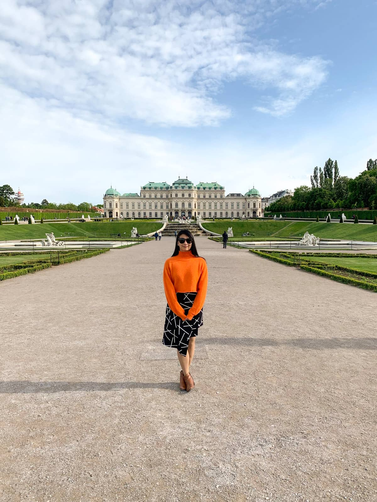 A woman wearing sunglasses, with an orange sweater and a black and white patterned skirt, standing in the middle of a wide path. The path leads to a palace in the distance, with green roofs. Beautiful gardens make up part of the grounds